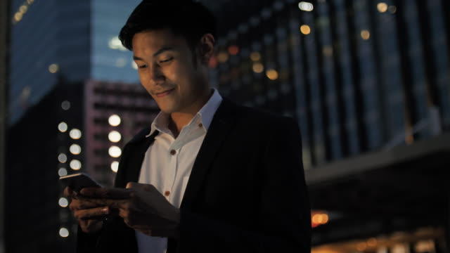 young businessman using phone at night - portability stock videos & royalty-free footage