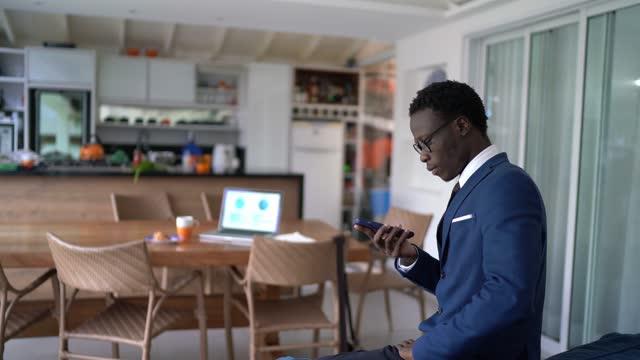 自宅で働くスマートフォンで歩いたりテキストメッセージを送る若いビジネスマン - 応答する点の映像素材/bロール