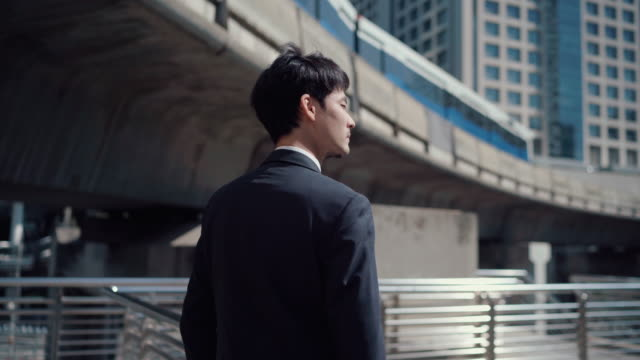 街の通りを歩く若いビジネスマン - 期待点の映像素材/bロール