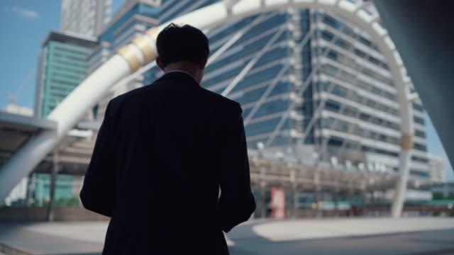 vidéos et rushes de jeune homme d'affaires marchant dans la rue de ville - one man only