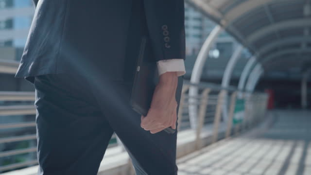 vidéos et rushes de jeune homme d'affaires marchant dans la rue de ville - un seul homme