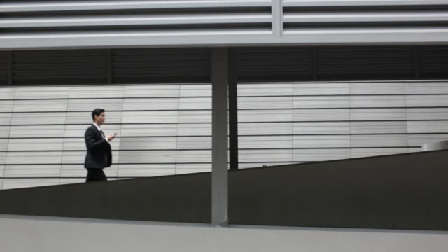 WS Young Businessman walking using smartphone