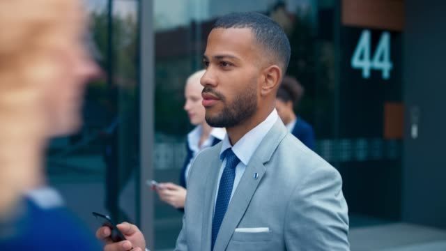 slo mo ts young businessman walking while scrolling his smartphone - corporate business stock videos & royalty-free footage