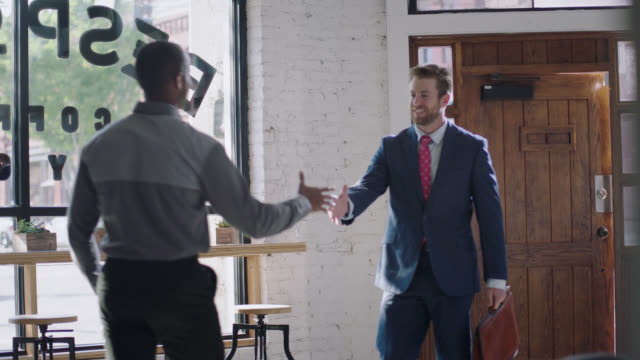 ws slo mo. young businessman walks into coffee shop and greets business partner with handshake. - hände schütteln stock-videos und b-roll-filmmaterial
