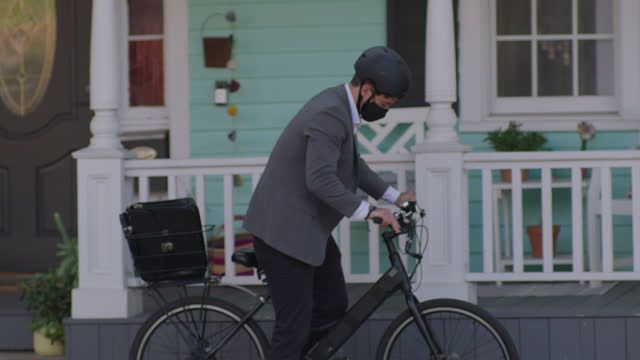 young businessman wearing face mask leaves house, puts on bike helmet, bikes away - leaf stock videos & royalty-free footage