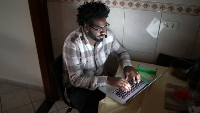 vídeos de stock e filmes b-roll de young businessman wearing headsets and working on a computer at home - afro