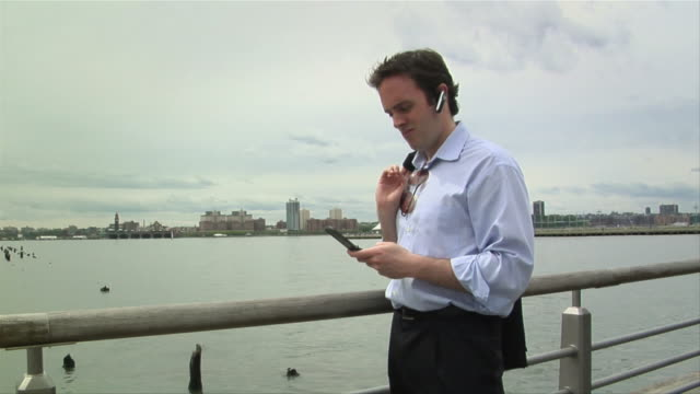 MS, Young businessman with Bluetooth headset text messaging on pier, New York City, New York, USA