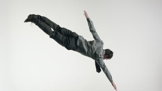 Young businessman with shirt and tie, doing acrobatics in the air