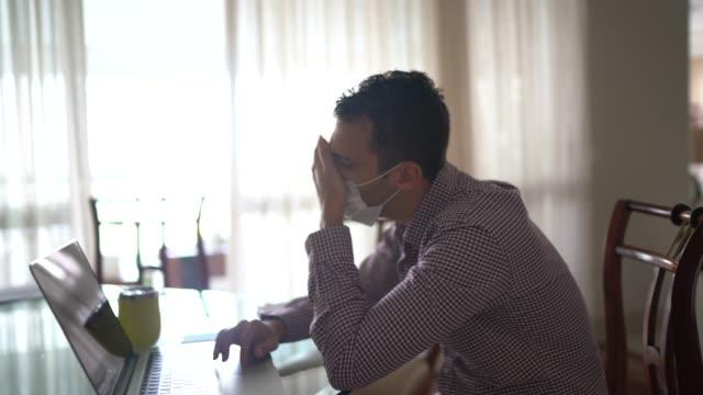 保護マスクを着用して自宅で働くしなこの痛みを持つ若いビジネスマン - 鼻腔点の映像素材/bロール