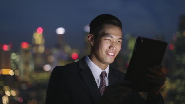 Young businessman working on a digital tablet at night.