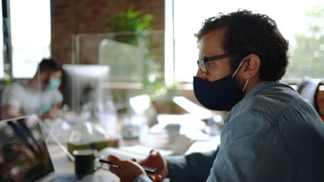 vídeos de stock e filmes b-roll de young businessman working on a laptop in the office - empregado