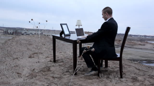 MS Young businessmand in black suit working on  his lap top while sitting at  table on top of  bluff in rural area  / Maple Grove, Minnesota, United States