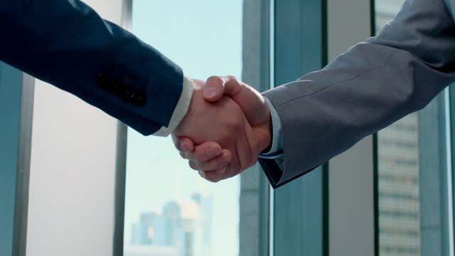 young businessmen shaking hands,4k - 拉近 個影片檔及 b 捲影像