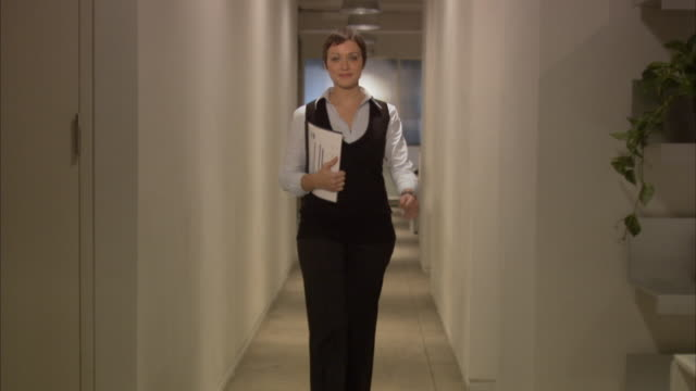 Young businesswoman carrying reports in office corridor, smiling / New York City, New York, USA