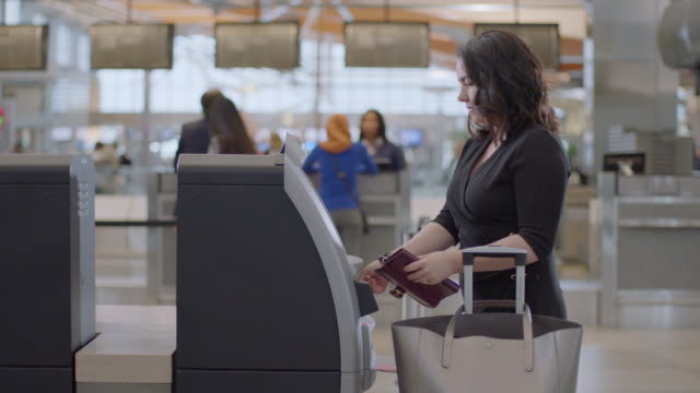 young businesswoman checks in using kiosk, retrieves boarding pass. - american culture stock videos & royalty-free footage