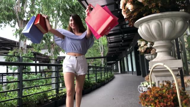 Junge geschäftsfrau fröhlich mit Einkaufstüten, Slow-motion