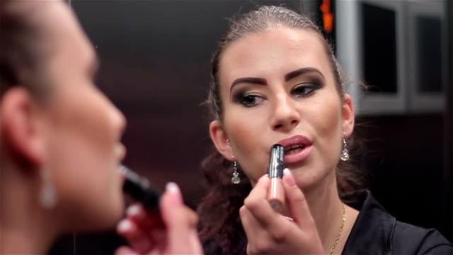 Jonge zakenvrouw corrigeert haar make-up in de Lift, close-up