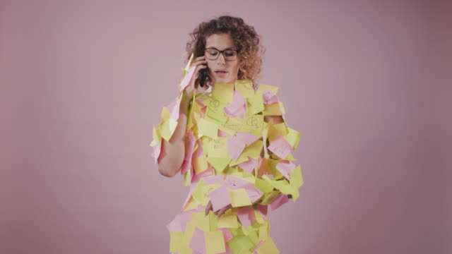 young businesswoman covered in sticky notes talking on smart phone. - gereiztheit stock-videos und b-roll-filmmaterial