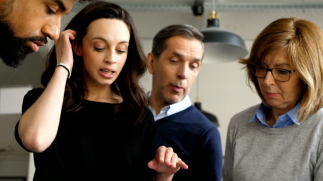 Young businesswoman discussing with coworkers
