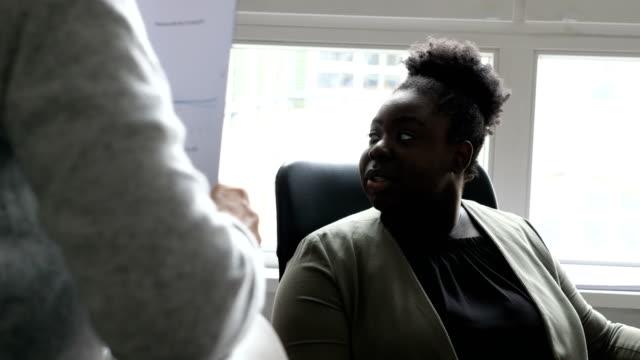 Junge geschäftsfrau diskutieren mit Menschen am Schreibtisch