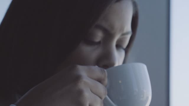 vidéos et rushes de young businesswoman drinking coffee at office - café boisson