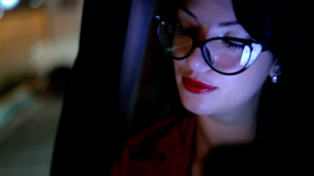 young businesswoman driving in a car on beck seat at night - eyesight stock videos & royalty-free footage