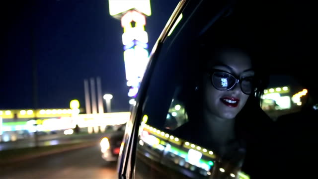 young businesswoman driving in a car on beck seat at night - expertise stock videos & royalty-free footage