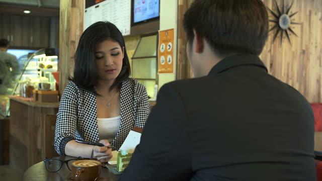 vídeos y material grabado en eventos de stock de joven empresaria durante la entrevista de trabajo en la cafetería - currículum vitae