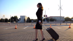 Young businesswoman going to taxi parking from the airport with her suitcase. Lady walking with her suitcase along street. Travel concept. Side view Slow motion close up