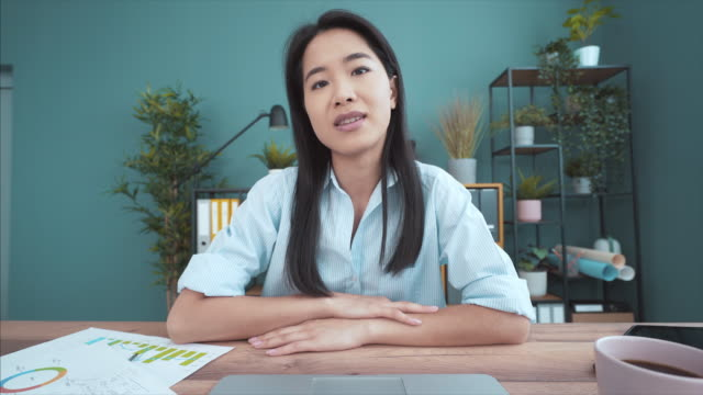 young businesswoman having a video call at the office. - south east asian ethnicity stock videos & royalty-free footage
