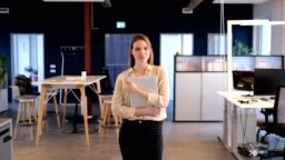 Young businesswoman holding laptop in new office