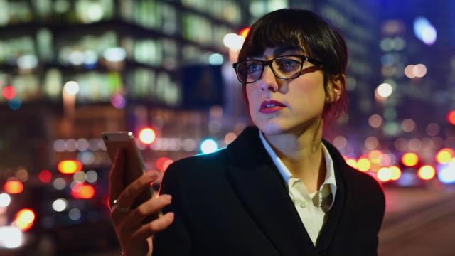 vídeos de stock e filmes b-roll de young businesswoman holding smart phone - trabalhadora de colarinho branco