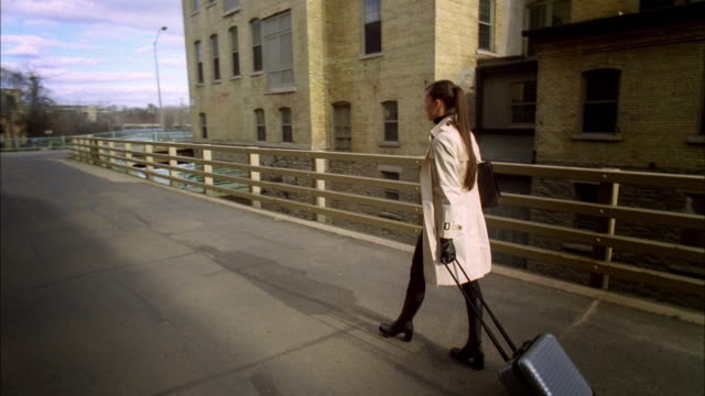 ws pov pan slo mo young businesswoman in trench coat walking with briefcase / madison, wisconsin, usa - トレンチコート点の映像素材/bロール