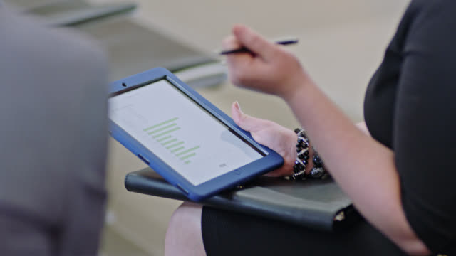 young businesswoman inspects date using tablet during discussion with colleagues at airport gate. - flugpassagier stock-videos und b-roll-filmmaterial