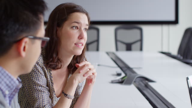 MS Young businesswoman leading team discussion during meeting with coworkers in conference room