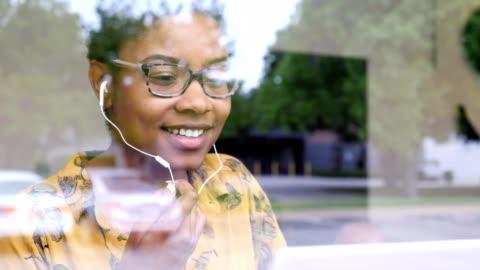 vídeos de stock, filmes e b-roll de a mulher de negócios nova participa na videoconferência quando na cafetaria - videoconferência