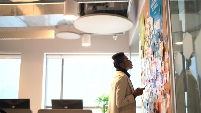 vidéos et rushes de planification de jeune femme d'affaires avec la tablette numérique ayant de nouvelles idées près du tableau d'affichage au travail - panneau d'information