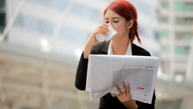 Young businesswoman reading newspaper and coffee