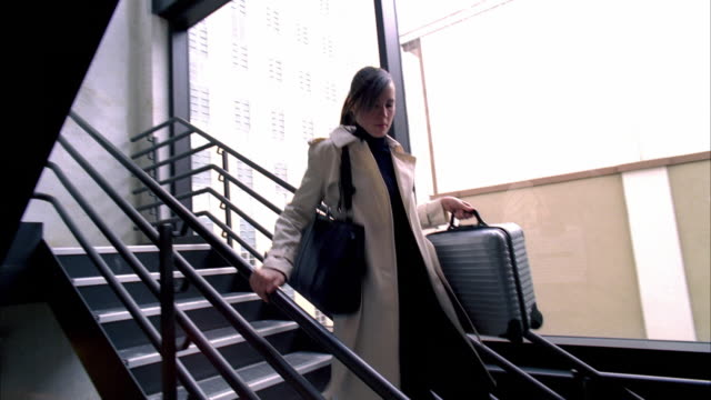 ms pan td young businesswoman running downstairs holding briefcase / madison, wisconsin, usa - andare giù video stock e b–roll