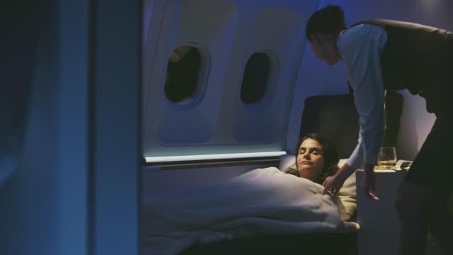 プライベート飛行機で寝ている若いビジネスウーマン - crew点の映像素材/bロール