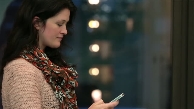 Young businesswoman smiles, reads and sends texts with smart-phone while waiting for someone