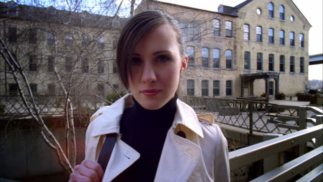 ms ds young businesswoman smiling / madison, wisconsin, usa - トレンチコート点の映像素材/bロール