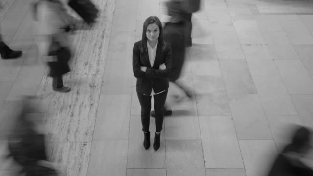 young businesswoman standing in public space. commuters walking in the background. black and white - arms crossed stock videos & royalty-free footage