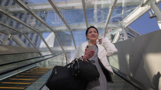 エスカレーターに立ち、電話で話す若いビジネスウーマン - 神奈川県点の映像素材/bロール