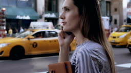 Young businesswoman talking on mobile phone, holding the documents. Female with smartphone in New York, America