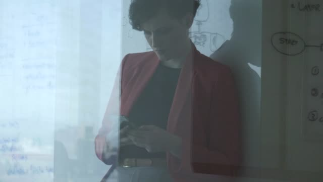 stockvideo's en b-roll-footage met young businesswoman text messaging on smart phone - blazer