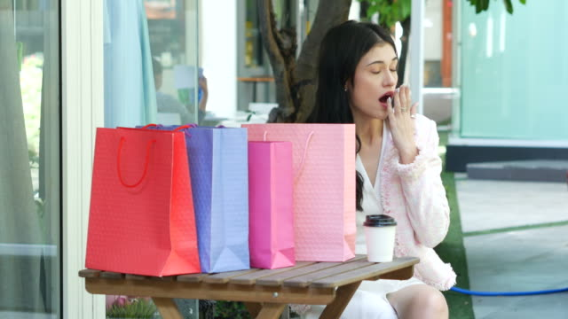 young businesswoman tried and yawning after shopping