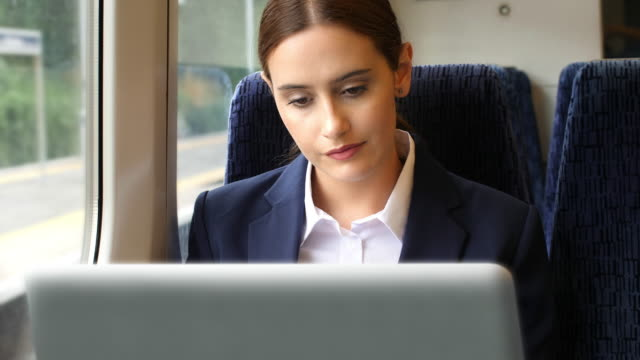 young businesswoman using a laptop on a train journey. sm. - rail transportation stock videos & royalty-free footage