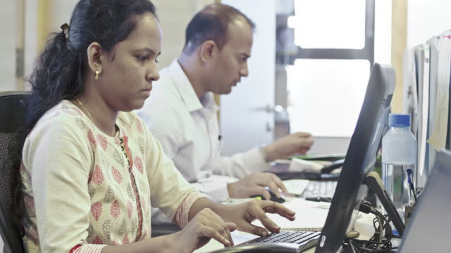 young businesswoman using computer at office - india video stock e b–roll
