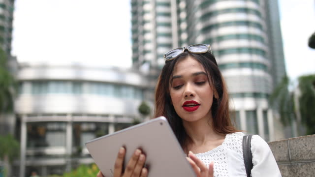 young businesswoman using digital tablet on her way to work - malaysian ethnicity stock videos & royalty-free footage